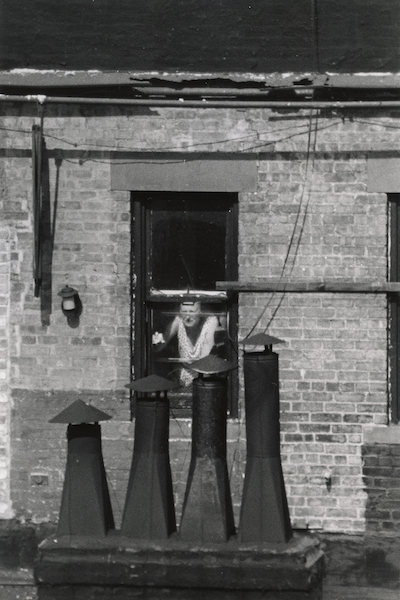 André Kertész - Woman at window with chimneys, 1970